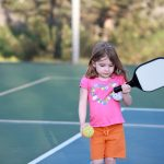 Cute Girl with Pickleball Paddles
